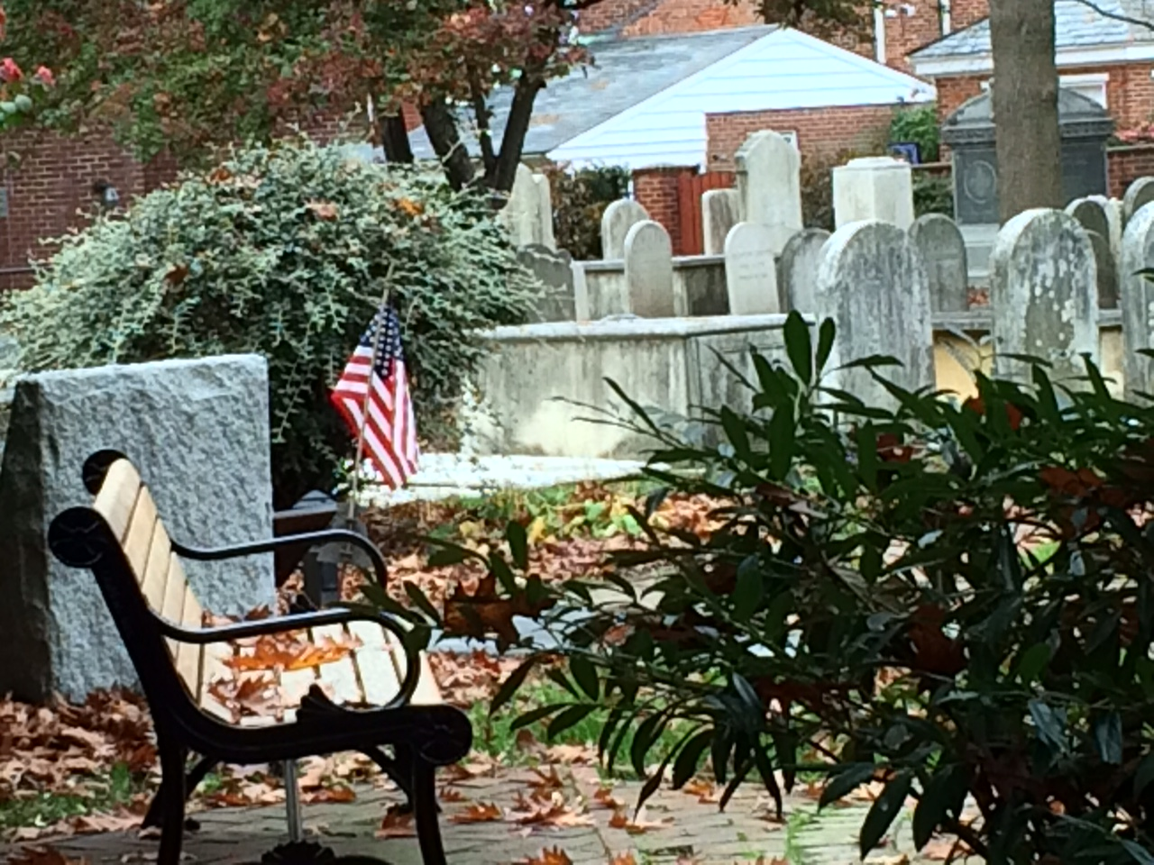 bench and graves at st. james cemetery in lancaster and american flag