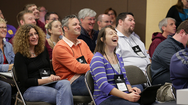 seated audience members laughing or smiling