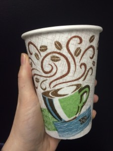 hand holding disposable coffee cup donna